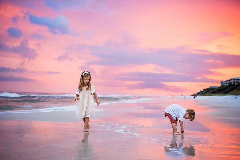 Two Kids play on the beach in Rosemary Beach FLorida with a pink and purple sunset by 30a photographer two lights photography