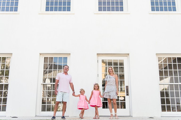 A family of four stands in front of the Rosemary Beach Town hall windows in a portrait session by Two Lights Photography