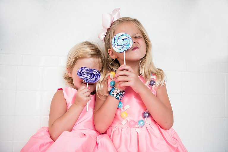 two sisters in pink dresses eating lollipops from the sugar shak at a family photography session by two lights photography